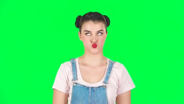 Thumbnail for Funny Girl Poses for Camera Makes Funny Faces on Green Screen at Studio, Slow Motion