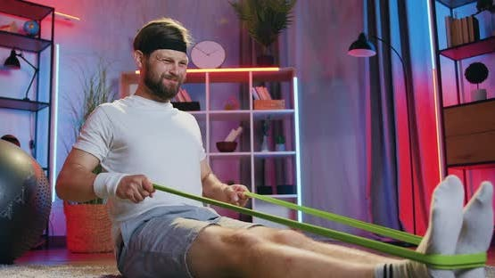 Man in Sportswear Doing Exercises with Rubber Resistance Strap on the Floor at Home in the Evening