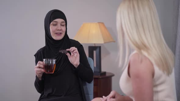 Thumbnail for Portrait of Happy Muslim Woman in Hijab Drinking Tea with Cookie and Talking with Blond Caucasian