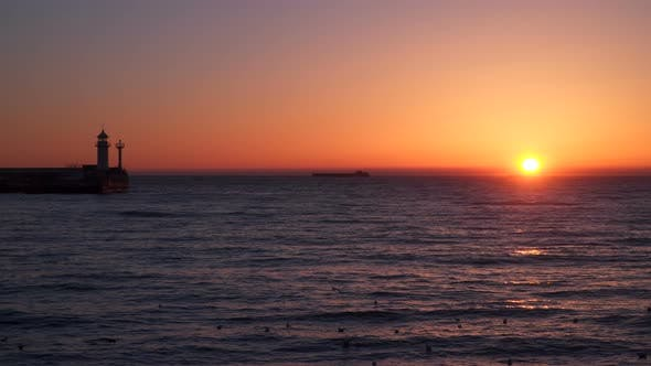 Thumbnail for Sunrise Over the Sea  We See a Cargo Ship On the Horizon  Pier With a Beacon