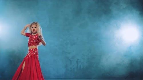 Beautiful Girl Blonde with Long Hair Dancing Belly Dance in Tubers of Smoke