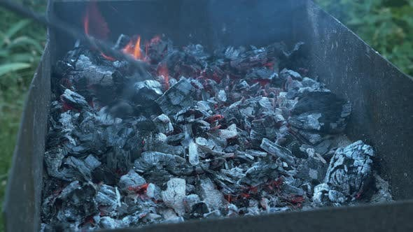 Coals burning in grill. Grill with hot coals. Smoke from a fire.