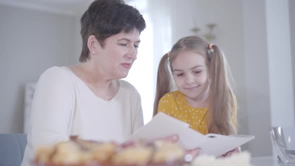 Adult Brunette Caucasian Woman and Little Girl Discussing Recipe of Pancakes for Shrove Tuesday