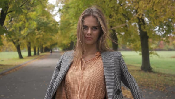 Thumbnail for Close-up of a Slim Caucasian Woman in Checkered Jacket and Mustard Dress Turning Around