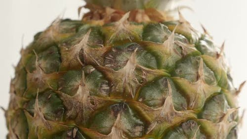 Crown and fruit texture  of tropical pineapple 4K 2160p 30fps UltraHD tilting footage - Ananas comos