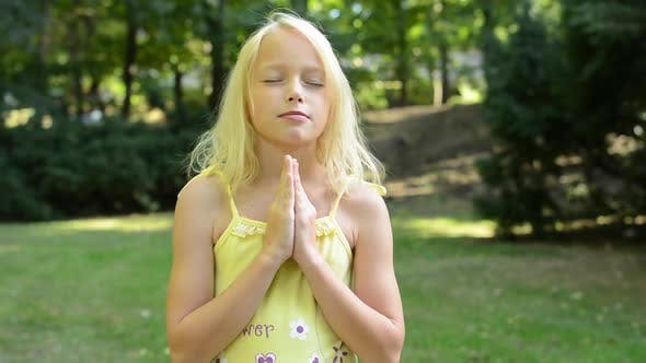Thumbnail for Little Cute Girl Prays in the Park with Prayer Hands Together