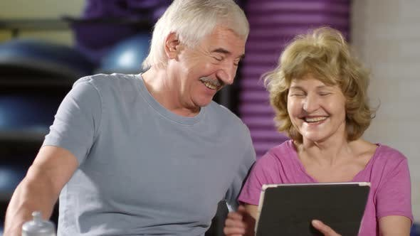 Thumbnail for Aged Couple Using Tablet in Sports Hall