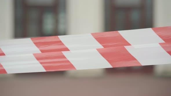Nahaufnahme von rotem und weißem Barrikadeband mit verschwommenem Stadtbau im Hintergrund.  Stadt