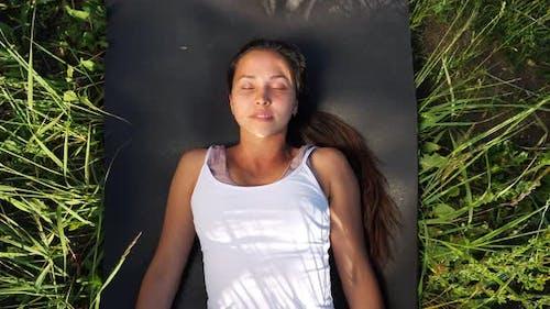 Beautiful Woman Lies on a Gymnastic Mat Among the Grass