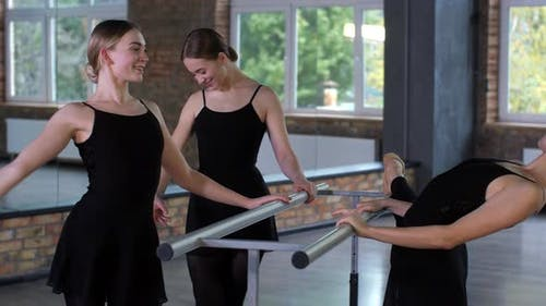 Joyful Ballerinas Chatting During Warmup at Barre
