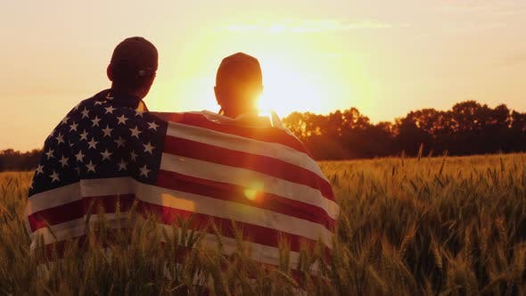 Thumbnail for Two Men with the Flag of America on Their Shoulders Look at the Sunrise Above a Wheat Field