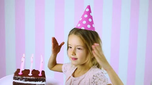Happy Surprise Close Eyes Little Girl in Pink Cap Blowing Out Candles on a Birthday Cake