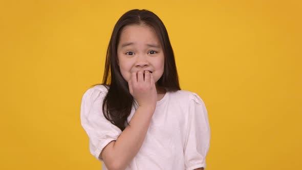 Little Asian Girl Feeling Panic Biting Her Nails Nervously Orange Studio Background Slow Motion