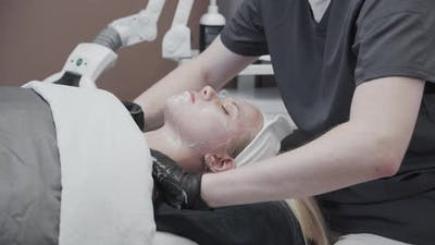Beautician Massaging Product Into Young Woman'S Face
