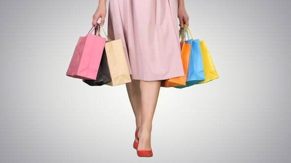 Thumbnail for Young Woman Legs Carrying Colorful Shopping Bags on Gradient
