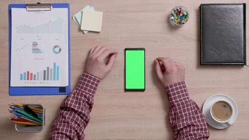 Draufsicht auf männliche Hände, die am oberen Rand eines Smartphones mit grünem Bildschirm scrollen