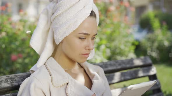 Portrait of Young Woman in Bathrobe with Towel on Head Got Shocking News While Sitting on the Bench