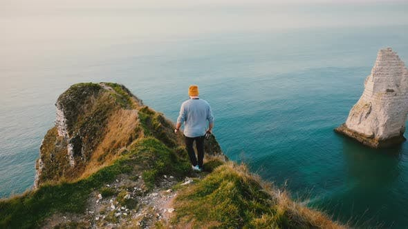 Thumbnail for Back View Young Tourist Man Walking Along Dangerous Path on Top of Normandy Coast Cliff To Enjoy