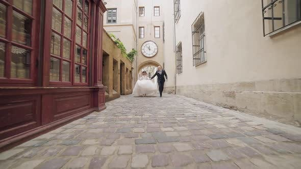 Thumbnail for Newlyweds Running in the Center of the Old Town. Bride and Groom. Wedding