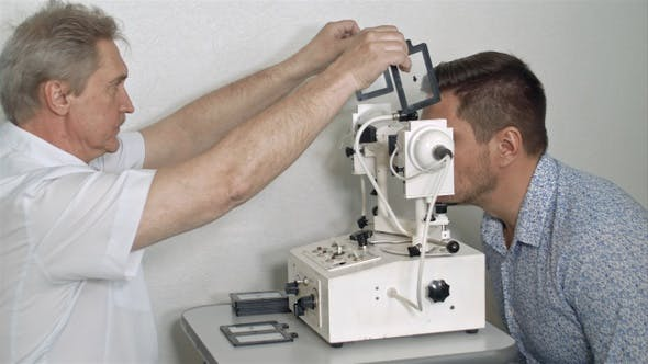 Male optician examining patient's eye pressure