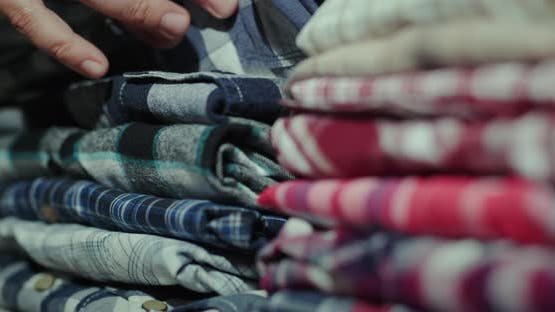 Men's Hands Sort Clothes in a Stack on the Shelf
