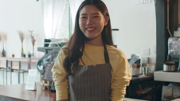 Asian woman barista feeling happy smiling at urban cafe.