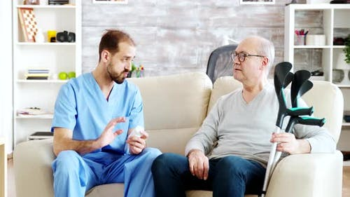 In Retirement Home Male Nurse Is Talking with an Old Disabled Man with Crutches Next To Him