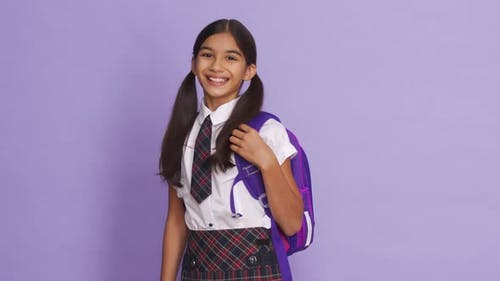 Happy Indian School Girl Wearing Uniform Holding Backpack on Lilac Background
