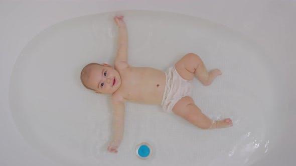 Draufsicht auf lustiges neugeborenes Baby, das während des Badens