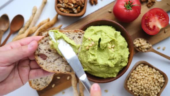Thumbnail for Hand Cooking Healthy Food By Spreading Avocado Smash On Toast