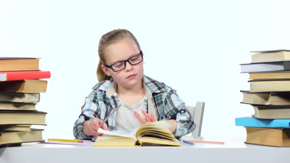 Thumbnail for Girl Sits at the Table Leafing Through the Book. White Background
