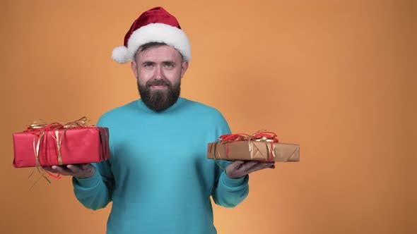 Man in Santa hat hesitates what present to give
