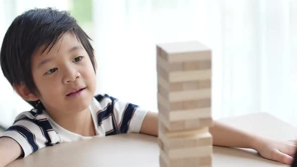 Cute Asian Child Playing Wood Blocks Stack Game