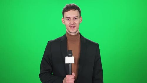 Man Reporter in Suit Looks Into the Camera and Speaks Into a Microphone on a Green Background a