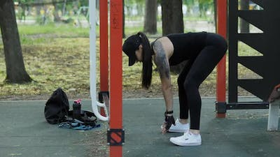 Athletic Woman Warming Up Before Training on the Playground in the Park