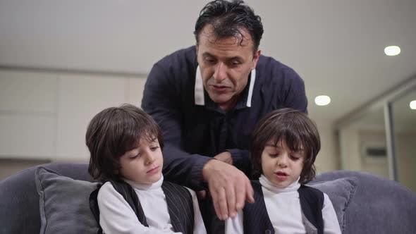 Portrait of Happy Middle Eastern Father Talking with Twin Sons Sitting on Couch