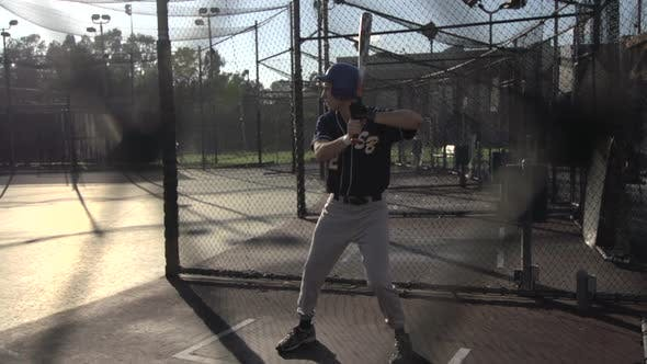 Thumbnail for A young man practicing baseball at the batting cages.