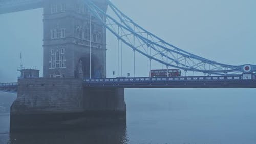 Coronavirus Covid-19 lockdown day one in foggy weather conditions at Tower Bridge in London, with Re
