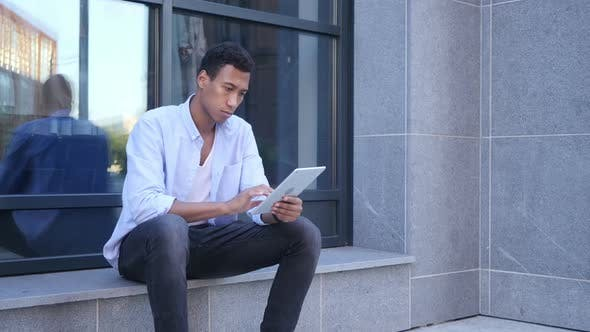 Cover Image for Outdoor Browsing on Tablet Computer, Young Black Handsome Man