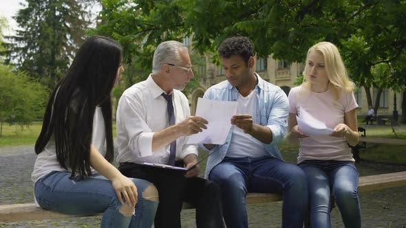 Thumbnail for Multi-Ethnic Students Giving Thesis Plans to Their Teacher, Higher Education