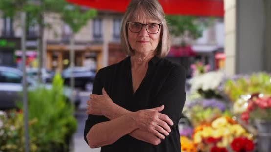 Thumbnail for Serious senior woman with arms crossed looking sternly outside city flower shop
