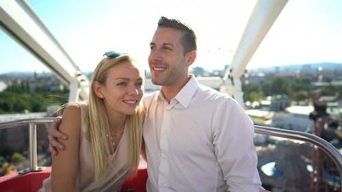 Happy Couple in Ferris Wheel High Above