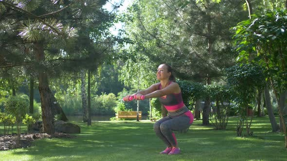 Thumbnail for Fitness Female with Dumbbells Squatting Outdoors
