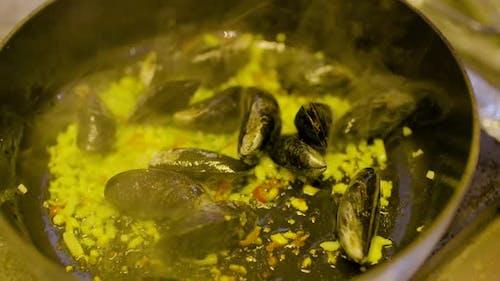 der Koch kocht Muscheln in der Pfanne