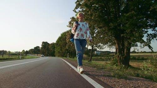 Woman with Backpack Walking on Roadside.