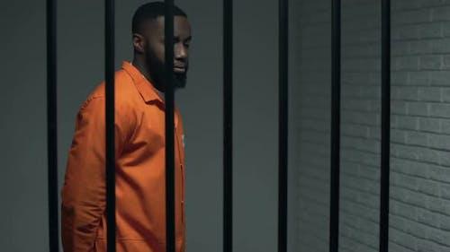 Nervöser schwarzer Gefangener wartet auf Satz in Einzelzelle, verurteilter Verbrecher