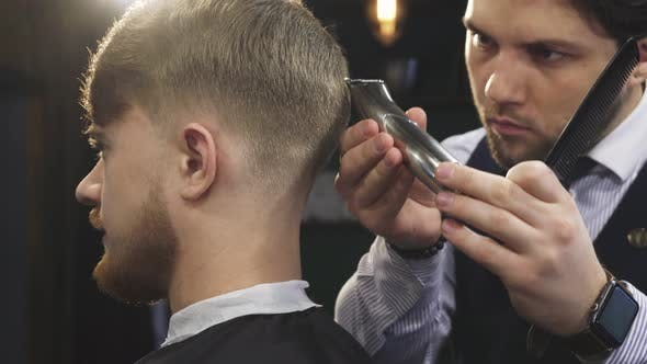 Cover Image for Handsome Professioanl Barber Stylign Hair of a Man