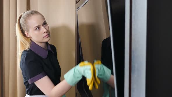 Cleaning in Modern Hotel. Housemaid in Gloves Wipes TV with Rag in Room of Residence Building. Dust