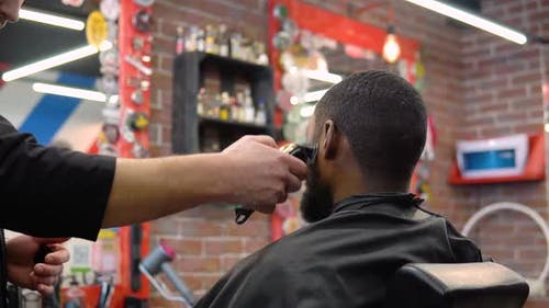 The Hairdresser Cuts the Client's Beard with a Clipper