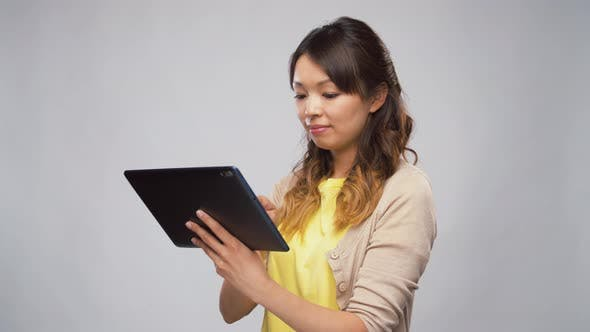 Cover Image for Asian Woman Using Tablet Computer